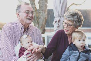 grandparents holding two small grandchildren