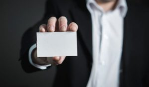 man in suit holding blank business card